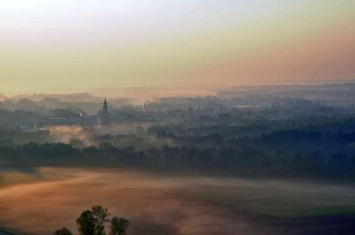 Altmühldorfer Tal mit der sog. Kilometerwiesn im Frühdunst. Aus dem Morgennebel wächst die Mühldorfer Stadtpfarrkirche Sankt Nikolaus dem neuen Tag entgegen.