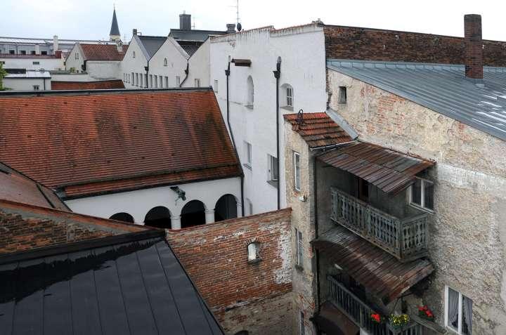 Renovierungsbedürftiger Stadthaus-Hinterhof - trotzdem werden die Balkonblumen gepflegt - Neben dem oberen Balkon die verwitterte Werbeschrift für ein früheres Gasthaus - Der nächste Hinterhof ist der Arkadenhof des Rathauses mit Wasserspeier-Drachen