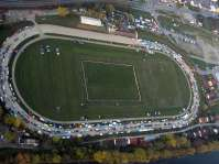 Die Pferde-Trabrennbahn in Mühldorf zog Jahrelang die Pferdefreunde und Totalisatorfreunde an. Aber auch die Sandbahn-Speedway-Motorradrennen - bis hin zur Weltmeisterschaft - wurden auf dieser Rennbahn abgehalten. Diese Aufnahme zeigt die ersten Oldtimer, die sich gerade zum Riesen-Oldtimermarkt entlang der Fahrbahn aufstellen. Zu späterer Stunde ist der gesamte Platz gefüllt. In der Mitte der Bahn ist der Fußballplatz der früheren Spielvereinigung Mühldorf, des jetzigen FC-Mühldorf erkennbar