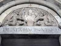 Nikolauskirche - Eingangspforte - In der Mitte des Tympanons wurde der runde Schlußstein aus dem früheren gotischen Kirchengewölbe eingefügt. Das Flachrelief aus dem Jahre 1440 stellt den heiligen Nikolaus dar; es wird von zwei knieenden Engeln gehalten.