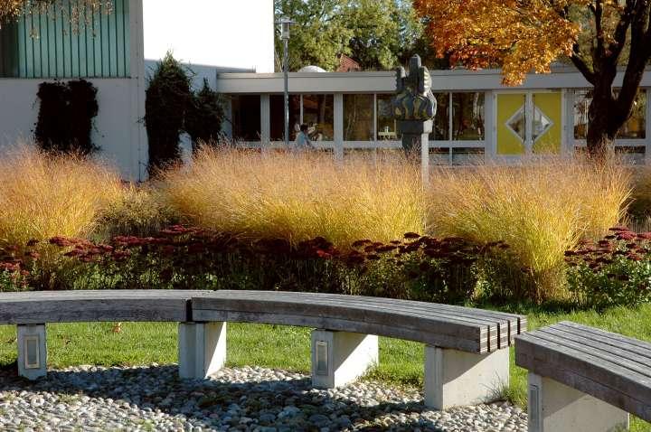Im Innstadtpark - Ruhebänke vor dem Findlingsbrunnen - im Hintergrund die Grundschule und die Phoenixfigur inmitten der herbstlichen Gräserbepflanzung