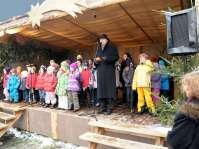 Mühldorfs Bürgermeister, Günther Knoblauch, eröffnet den Christkindlmarkt. Auf der Bühne der Kinderchor von Sankt Nikolaus, der die Gäste mit Weihnachtsliedern erfreut