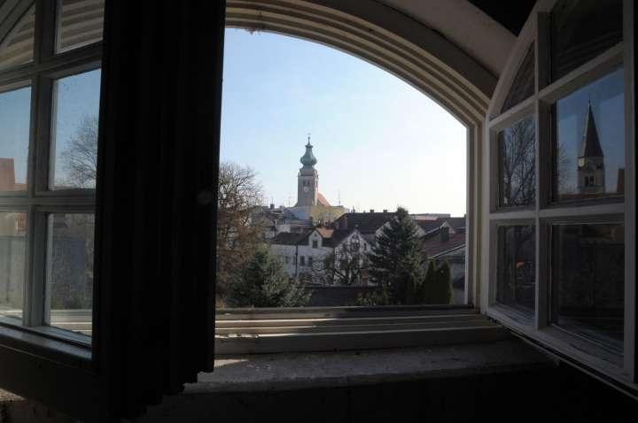 Ein Blick aus dem Dachgaubenfenster des Hans-Prähofer-Hauses an der Luitpoldallee gibt einen schönen Ausblick auf die Nikolauskirche frei. Im aufgeklappten Fensterflügel spiegelt sich der Turm der Frauenkirche