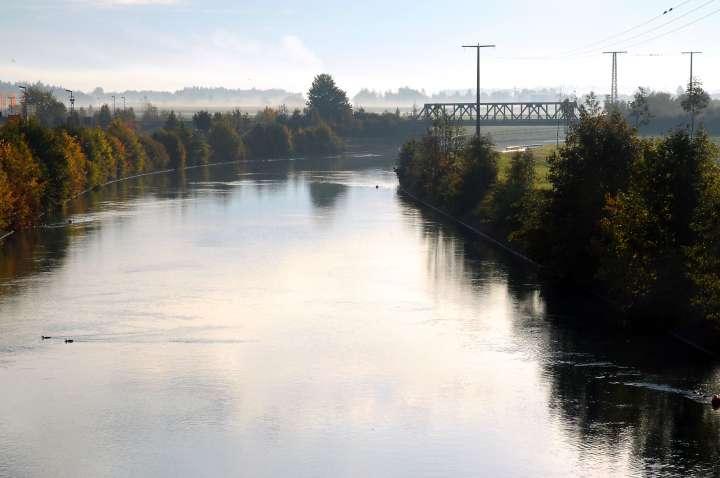 Träge fließt der Innkanal unter der Hölzlinger Eisenbahnbrücke hindurch Richtung Töginger Innkraftwerk. Die Enten genießen die ruhige Strömung über den Feldern steht der Frühnebel Anfang Oktober
