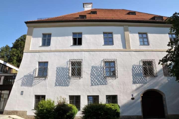 Die kunstvoll geschmiedeten unterschiedlichen Gitter vor den Pflegschlossfenstern am Katharinenplatz werfen ein interessantes Schattenbild an das alte Gemäuer