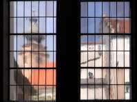 Fast schemenhaft, wie Gemälde, zeigen sich der Turm der Nikolauskirche und die Südfassade des Pfarrhofes dem Betrachter, wenn er durch die Fenster der Spitalkirche des Heilig-Geist-Spitals blickt