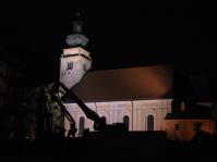Nikolauskirche Südansicht - Bedrohlich sehen sie aus, die Bau- und Abbruchmaschinen, wie sie sich als schattenhafte Umrisse vor der beleuchteten Kirchenfassade abheben. Diese Aufnahme entstand beim Abbruch des ehem. Caritas-Altenheim von der Spitalgasse aus