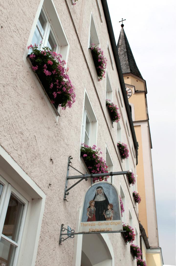 Bei vielen Mühldorfern dürfte dieser Anblick des früheren Stadtkindergartens, jetzt Gerhardinger Kindergarten, Erinnerungen wach rufen. Wie ein Wächter steht der Turm der Frauenkirche neben dem Kindergarten am Mühldorfer Stadtplatz