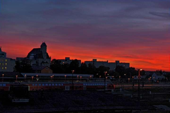 Glutrot färbt sich der Himmel im Westen und setzt das markante Gebäude der Walzmühle am Bahnhof Mühldorf mit der schönen Silhouette in Szene